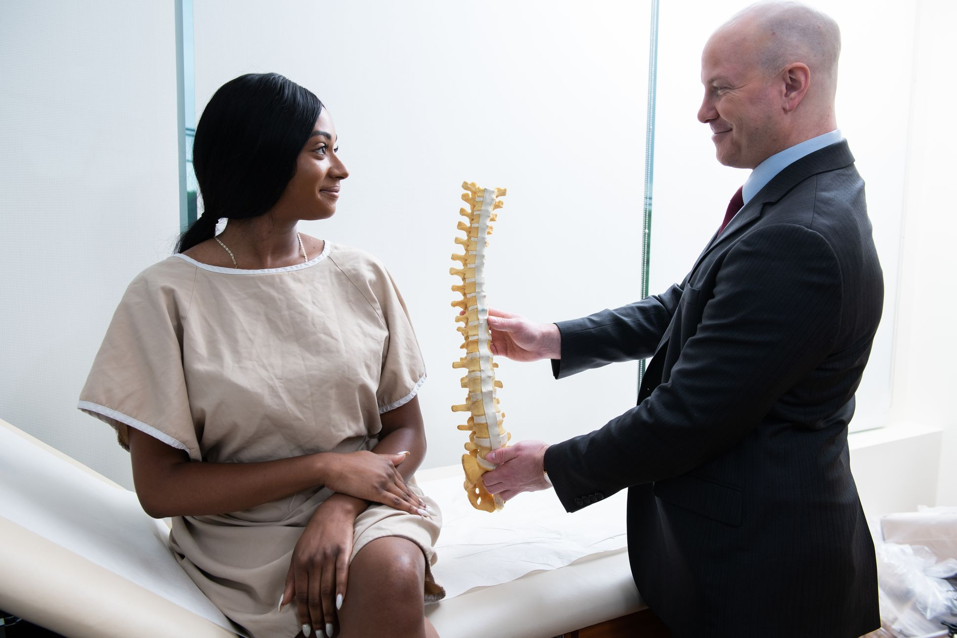 A doctor holds a model spine up to a female patient.