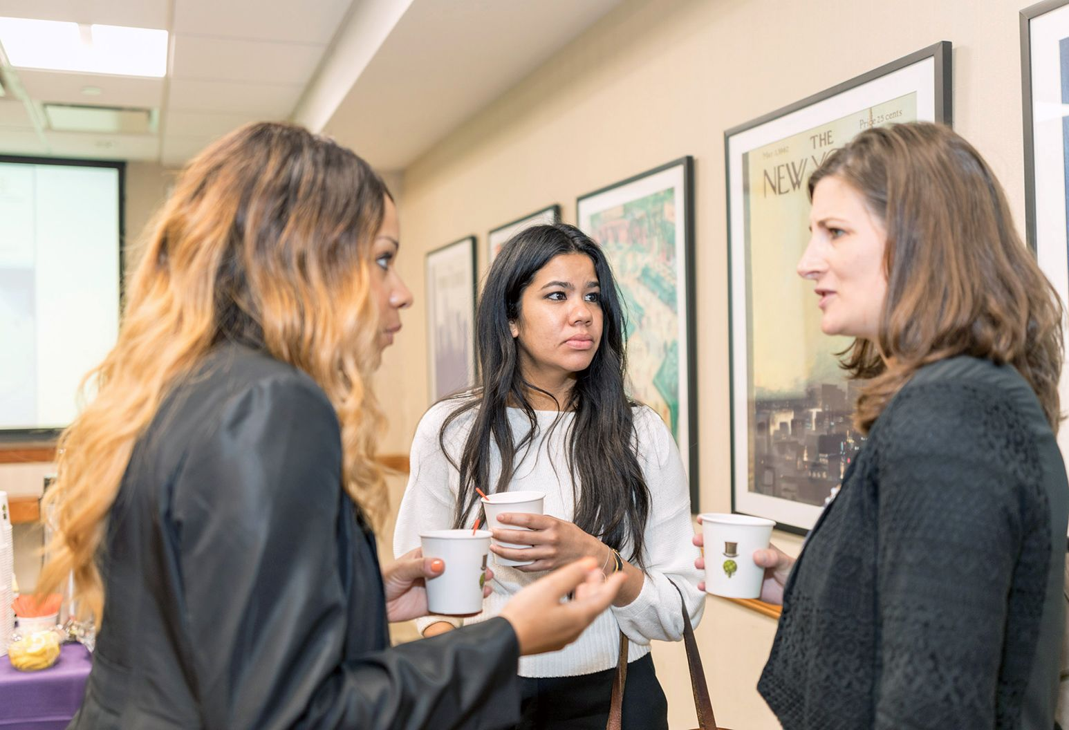 Three female professionals are talking in the hallway at a conference