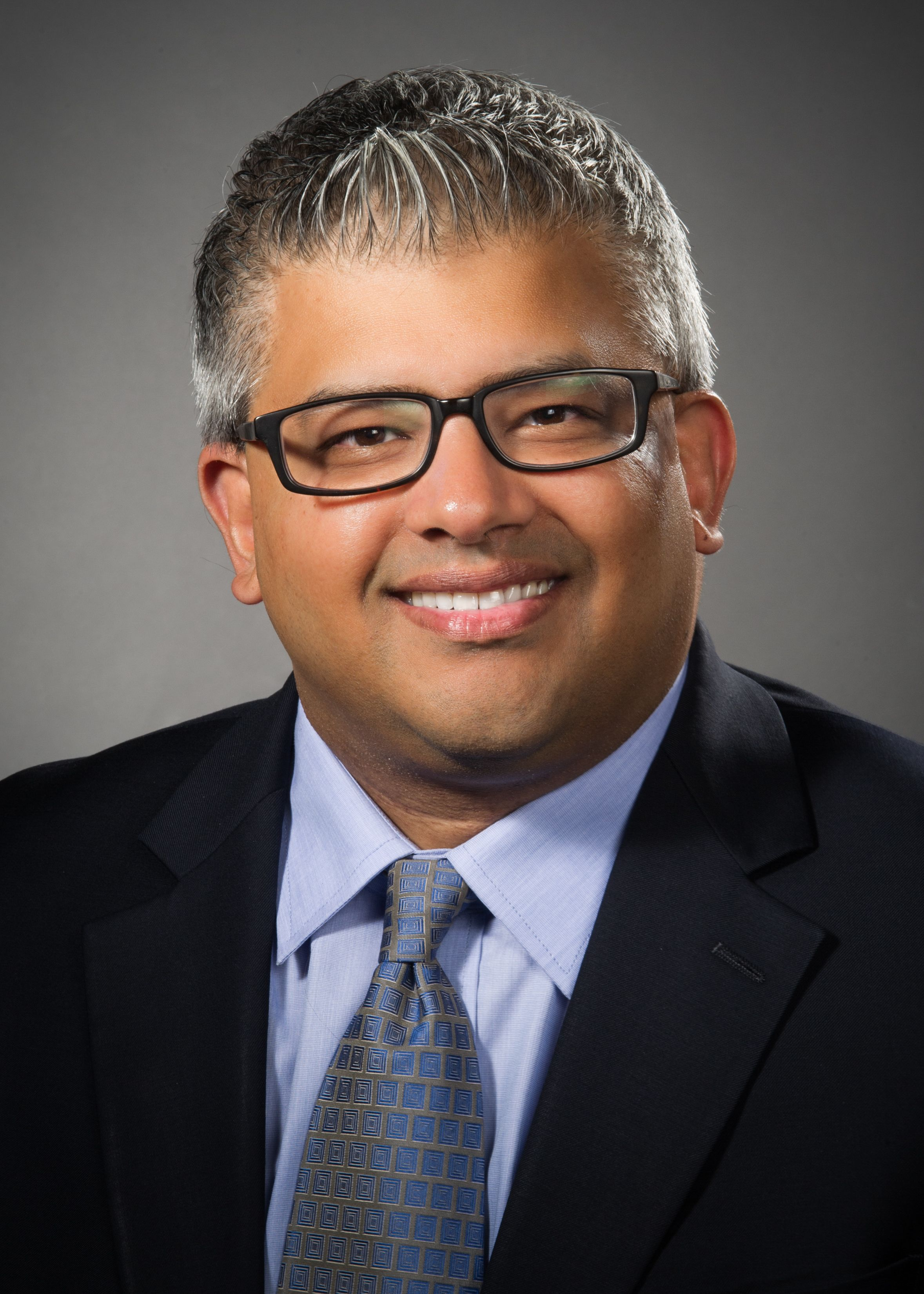 Amit Garg, MD, wearing a blue shirt and blue tie