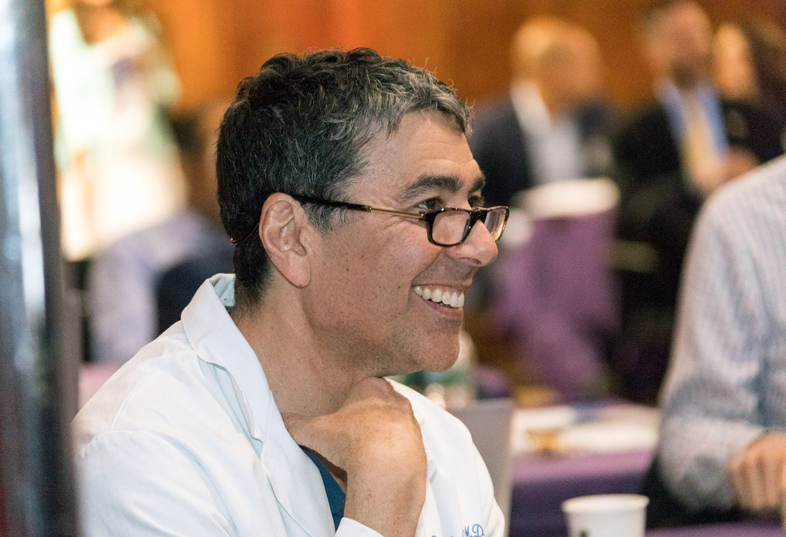 Close up photograph of a middle aged male doctor smiling while he is watching a presentation