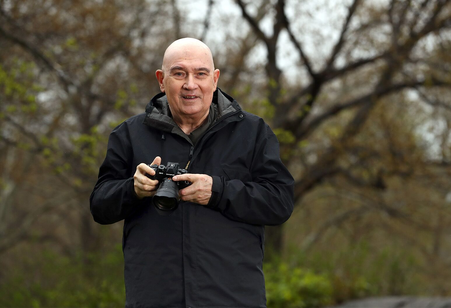 A man poses in the park with his professional camera.