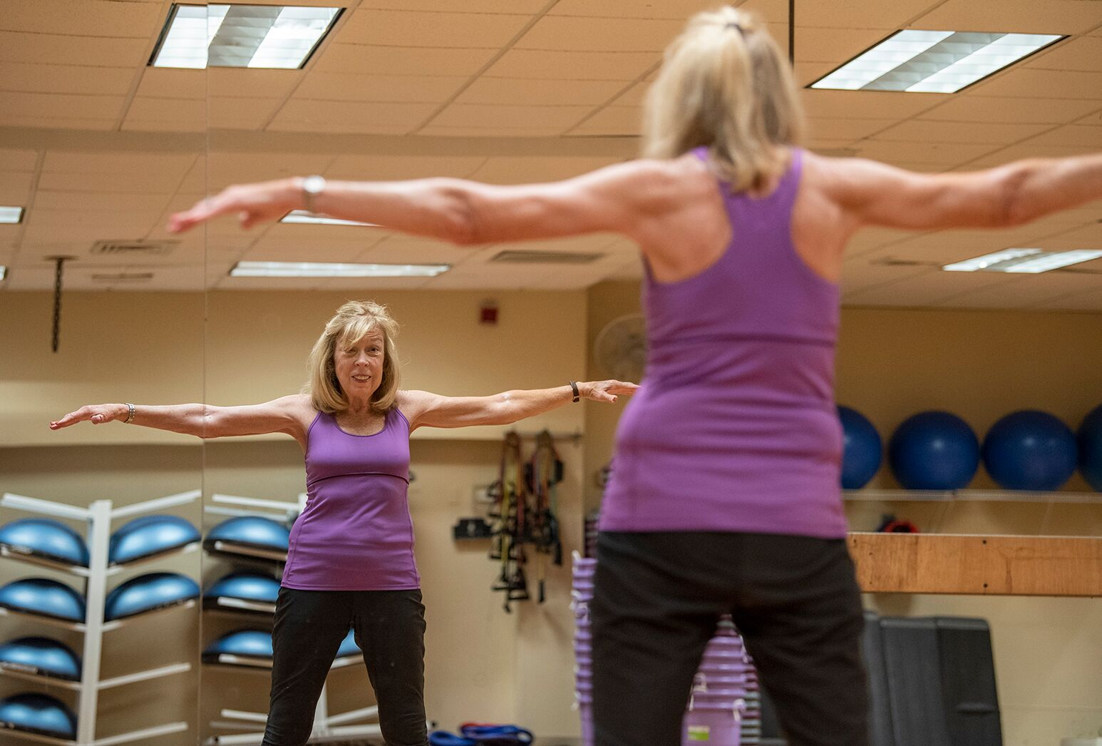 Blonde haired woman in purple tank top and black pants in front of a gym mirror.