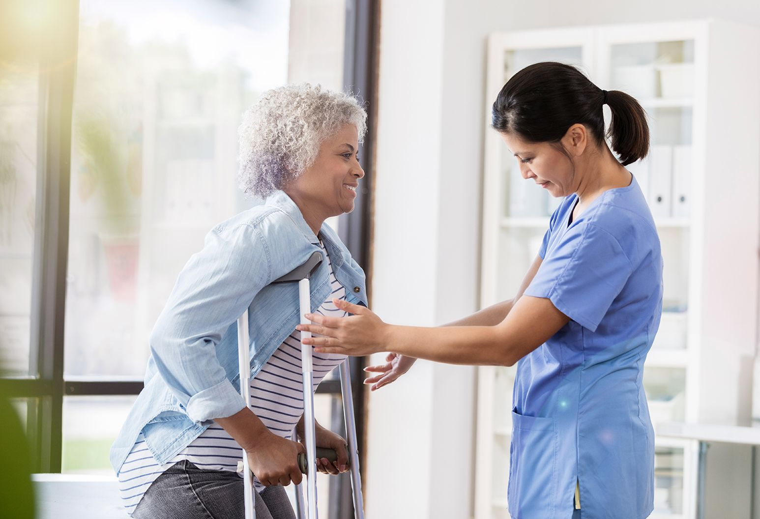 Senior woman on crutches works with a caring female physical therapist during her recovery process.