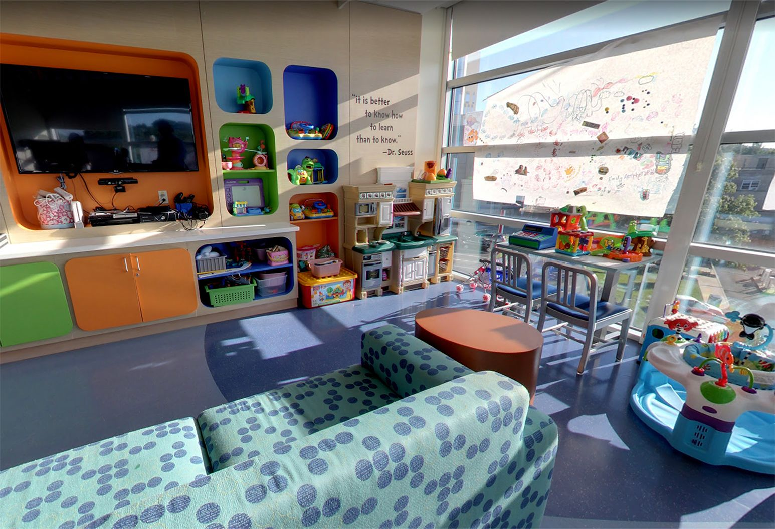 Our playroom features a cheerful orange, green and blue color scheme. It's filled with a big screen television, gaming consoles, toys and crafts. There is also large windows, a blue patterned couch and a table with chairs.