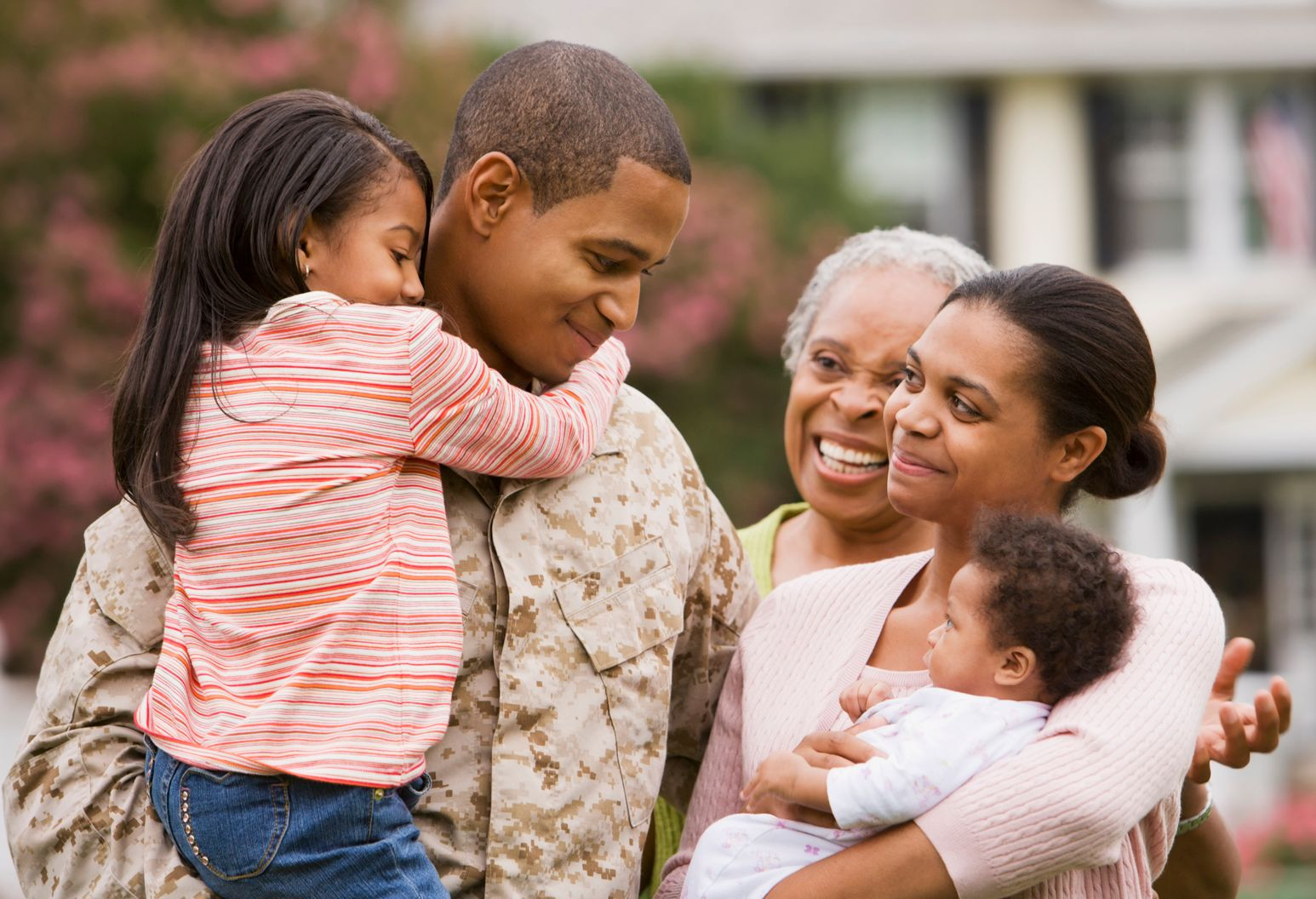 Soldier standing with his wife, two young children, and mother