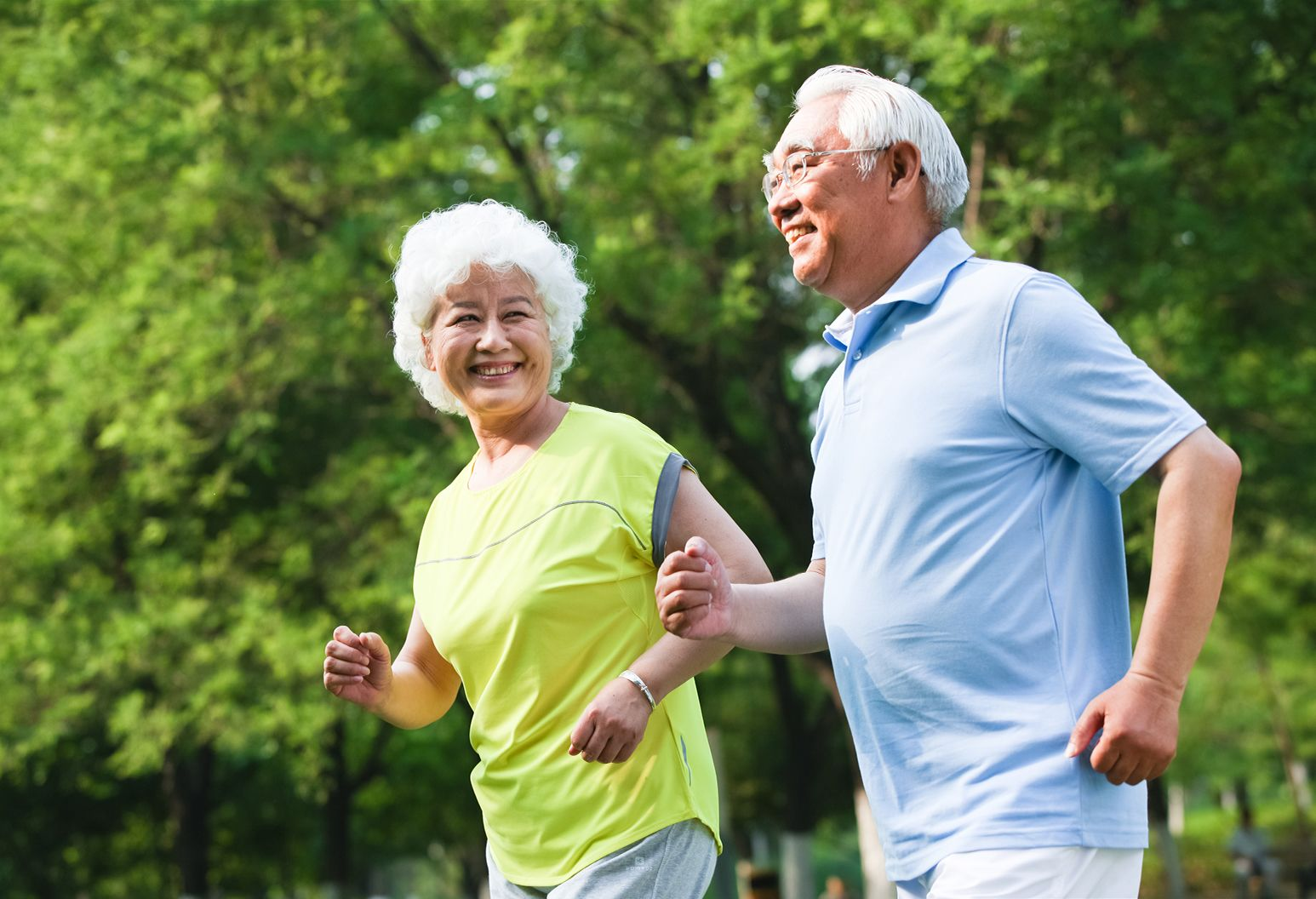 An elderly woman and man out jogging in a bright wooded area.