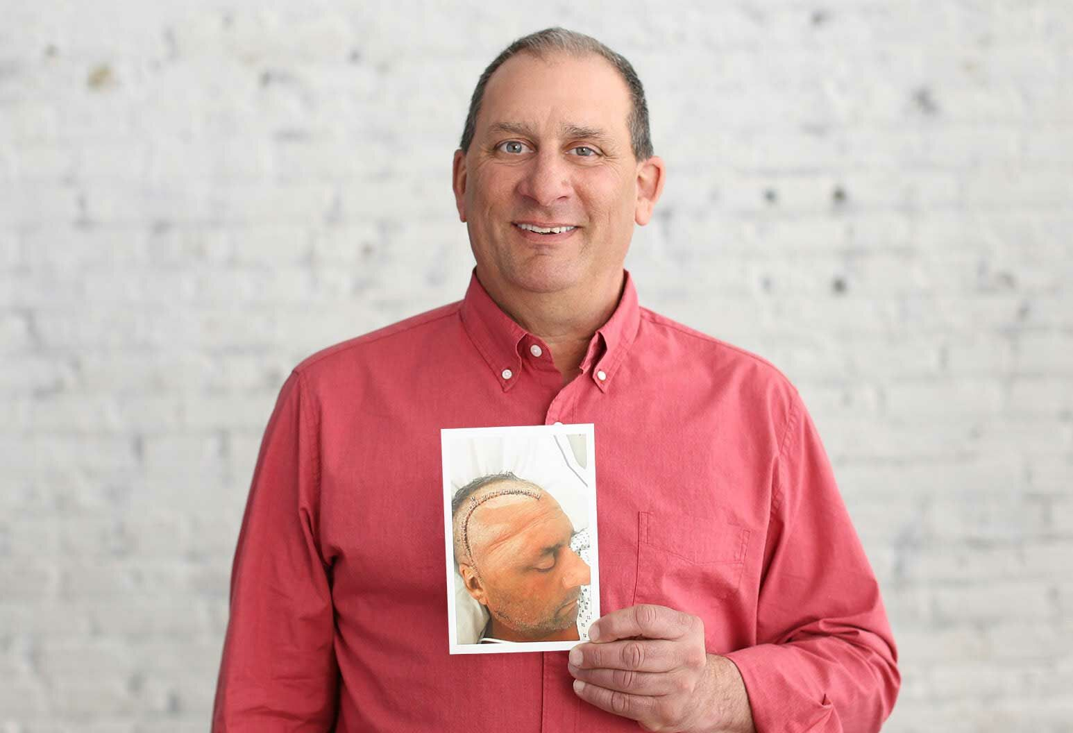 Patient in a coral colored shirt holding an image of himself after brain surgery.