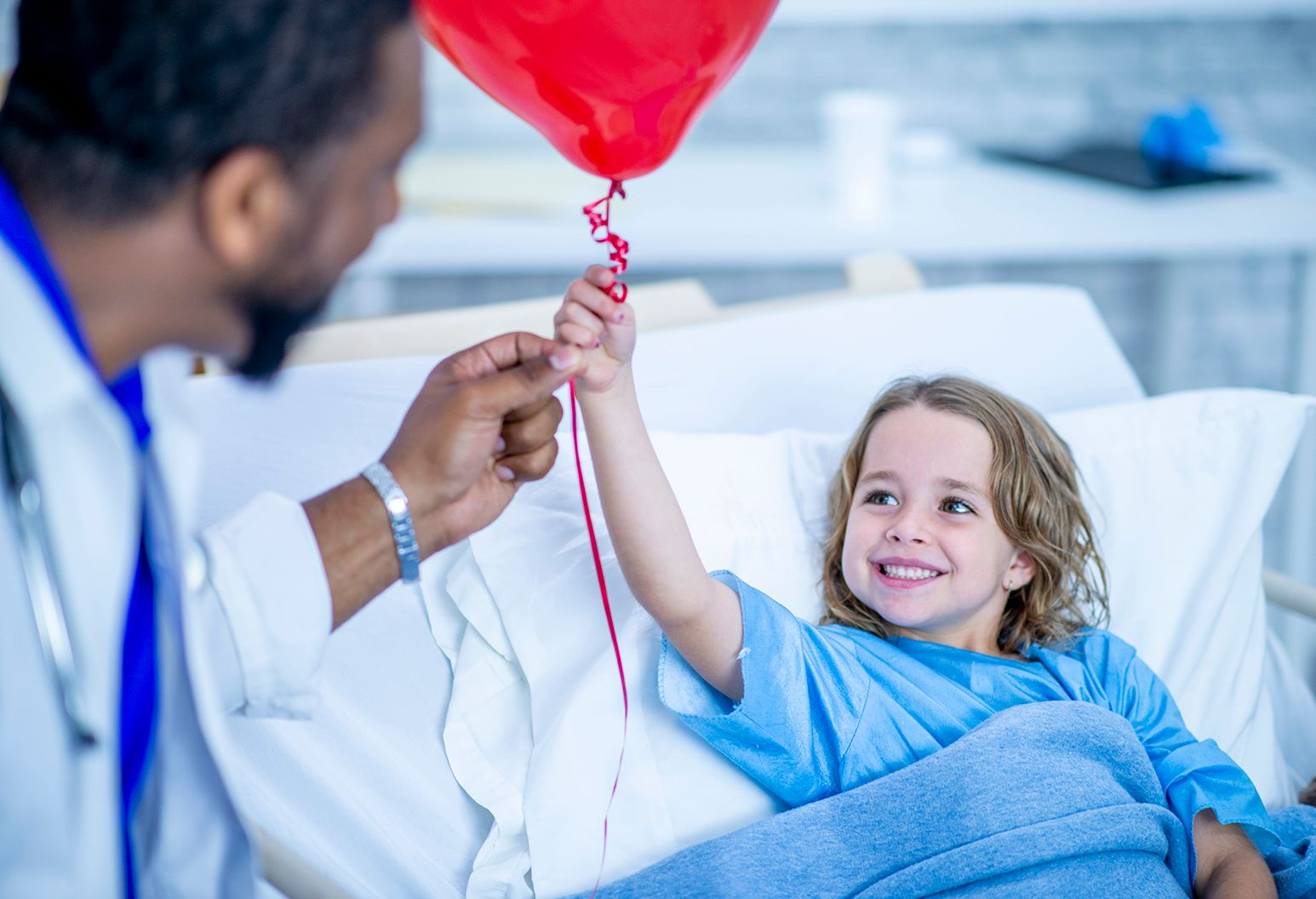 A young girl smiles adorably while taking a balloon from her doctor's hand. The doctor is standing by her bed and wearing professional clothing.
