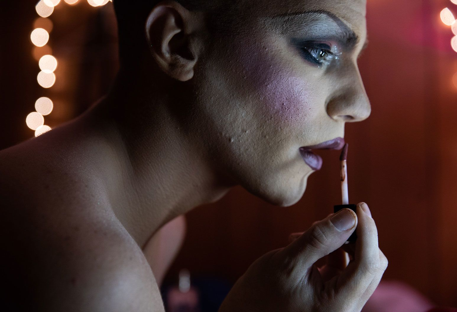 A man with drag make up on his face stares into the mirror as he applies lipstick.
