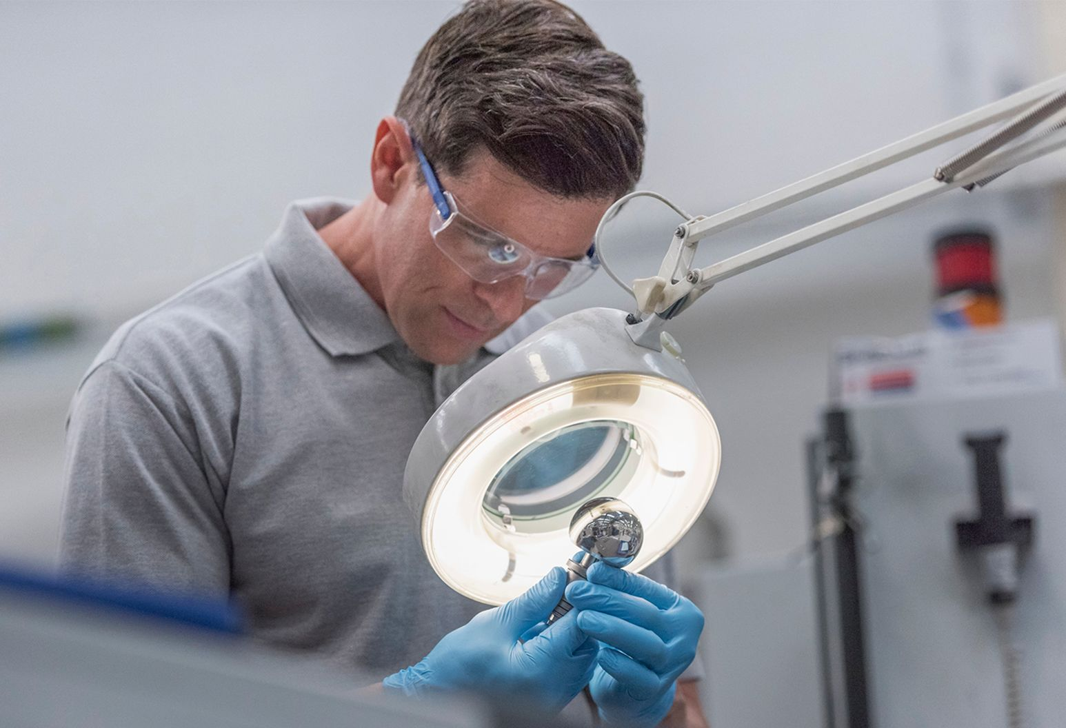 Man in grey shirt and safety glasses examining piece of technology under microscope