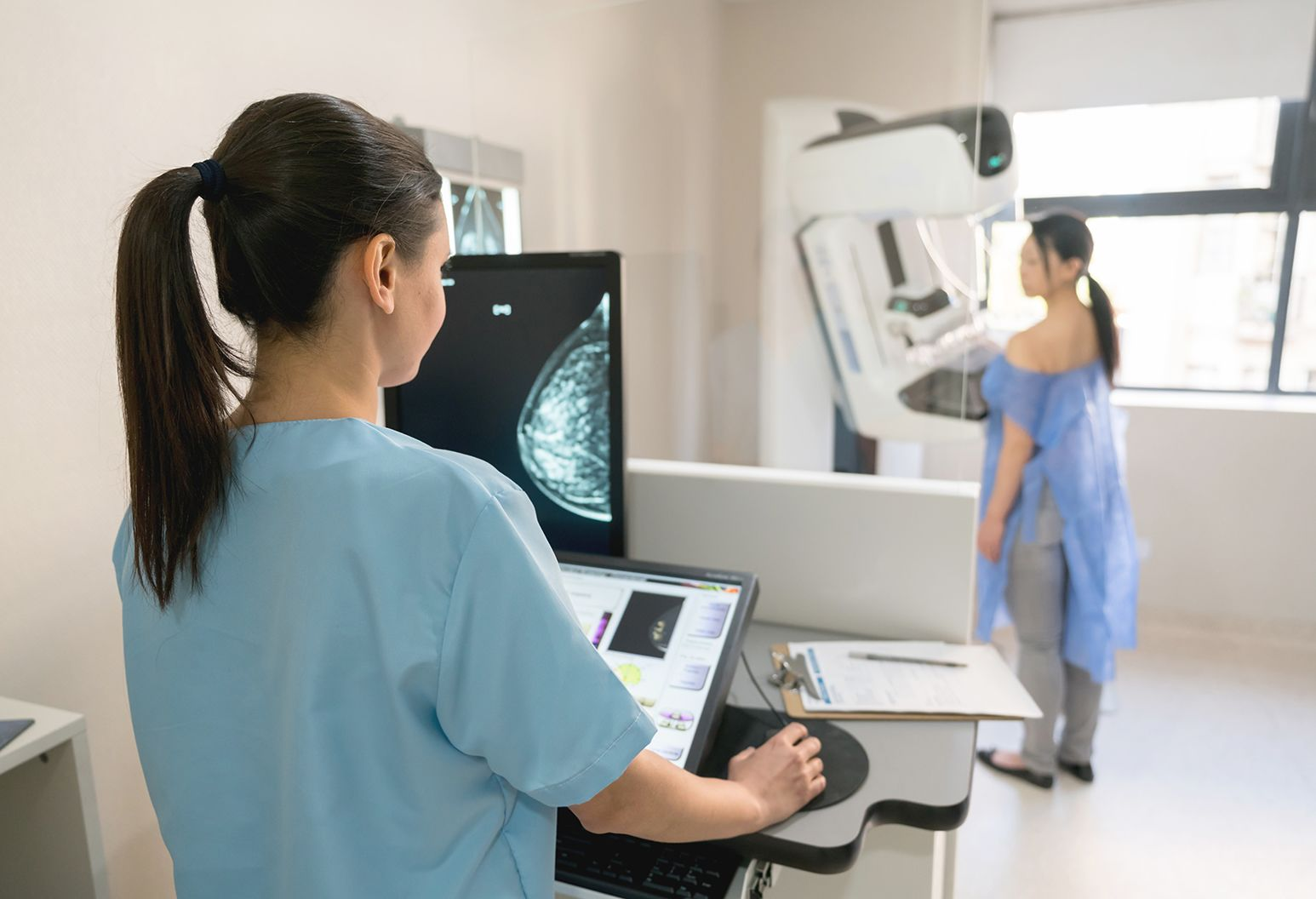 Unrecognizable nurse taking a mammogram exam to an adult patient at the hospital