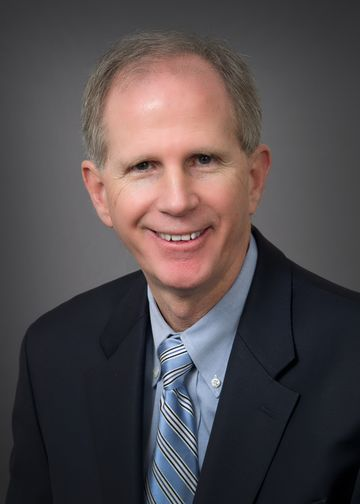 Robert Scanlon, MD, wearing a blue shirt and blue tie