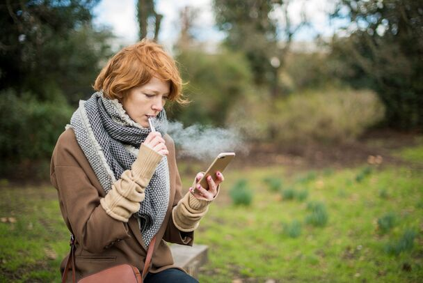 A woman vapes while holding a tablet.