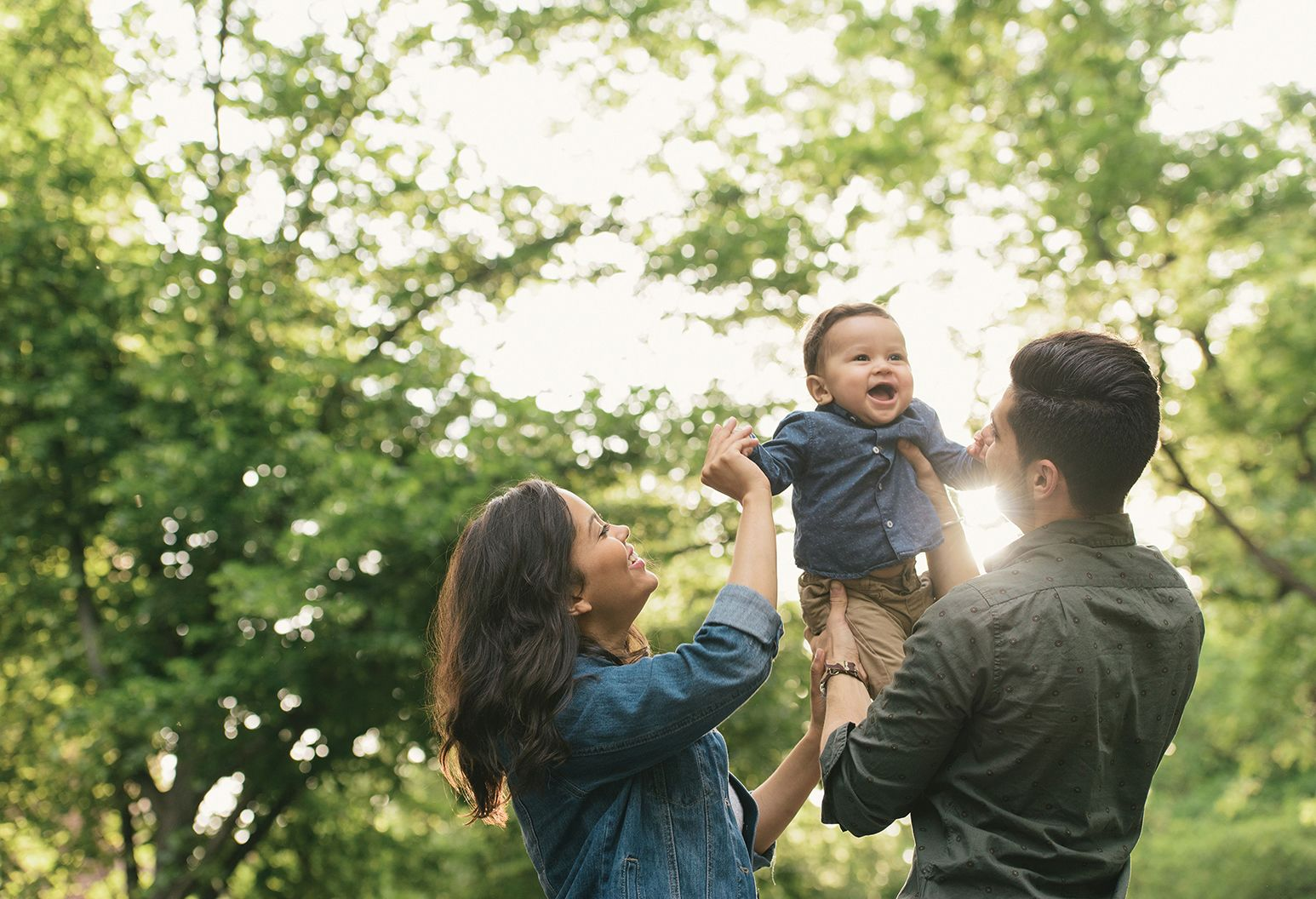 A six month old male child in a blue shirt and khaki pants is held in the air by his parents who are facing away from the camera. Ther mother has long dark hair and a blue shirt and the father has a green shirt. They are outside surrounded by trees.