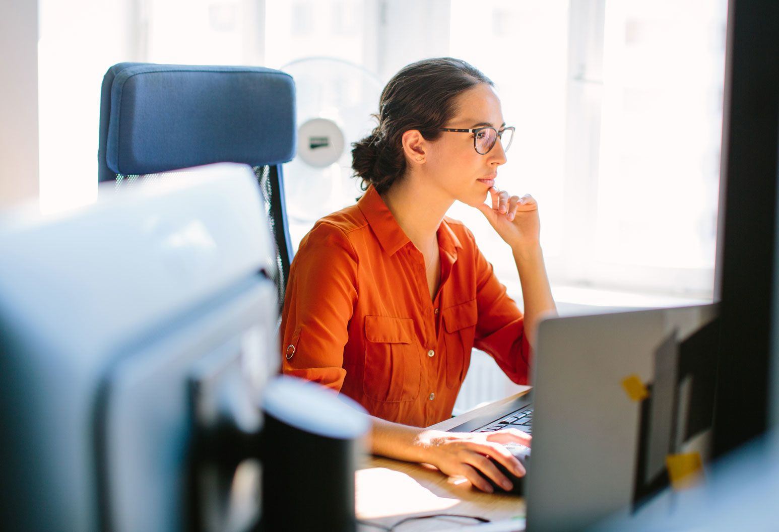 Woman sitting in front of computer thinking