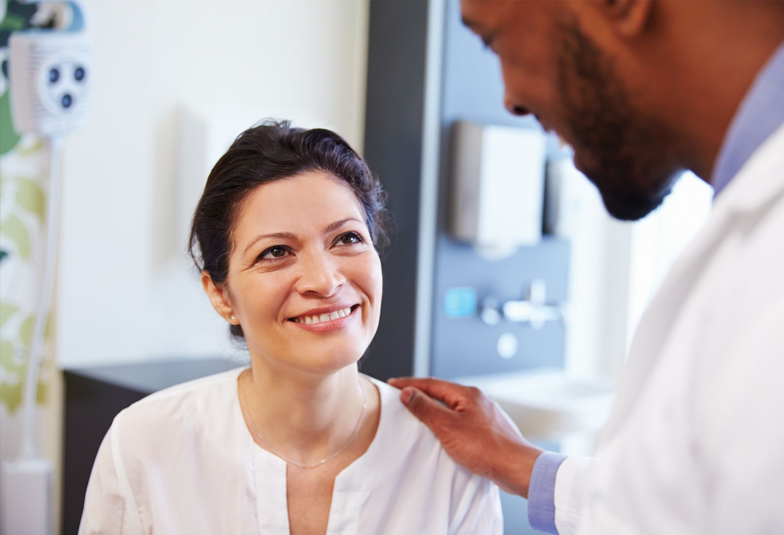 Middle aged woman with brown hair and white blouse smiles as doctor in white lab coat talks to her while gently touching her shoulder.