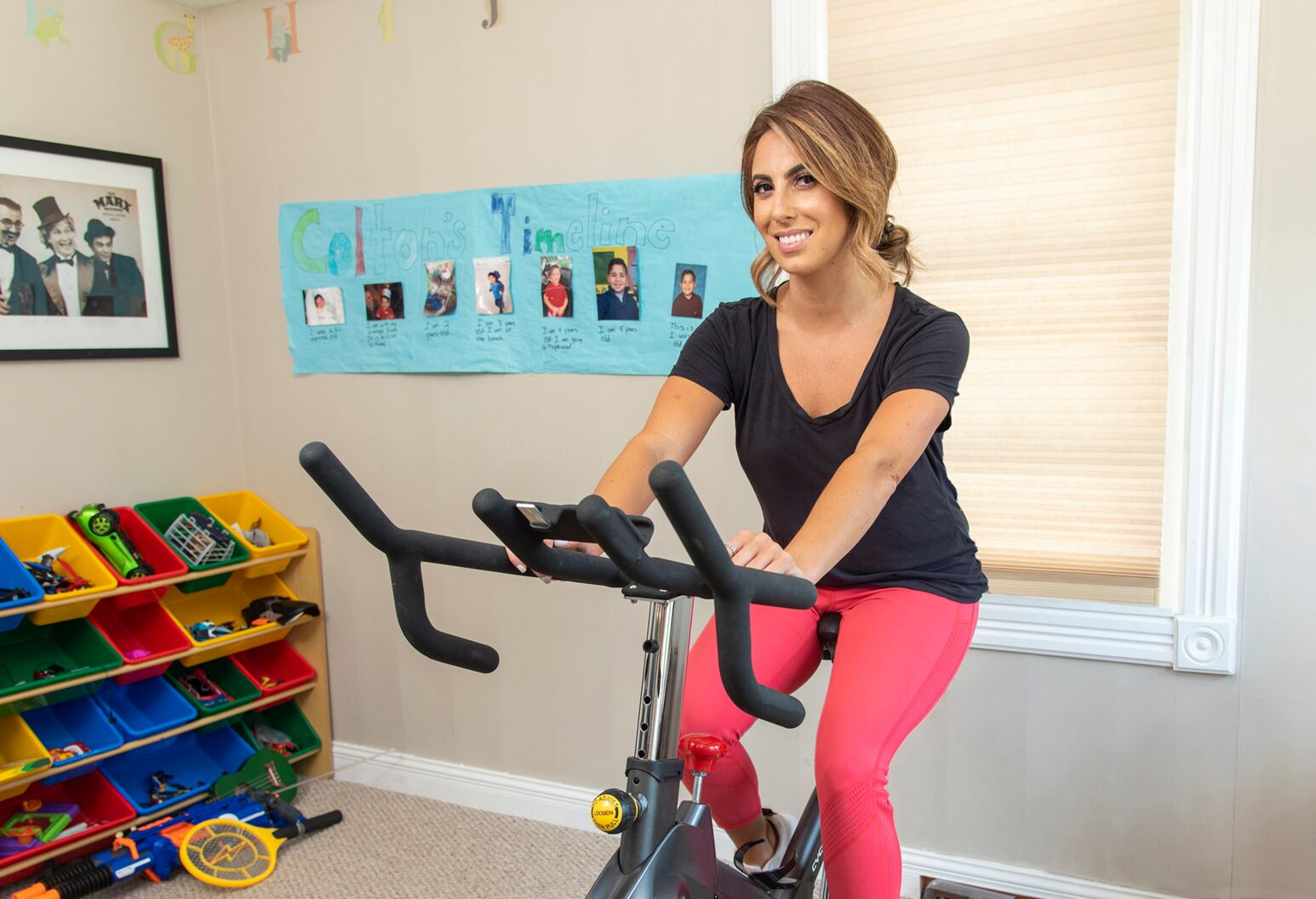 Woman in her late 20s in pink tights and black shirt on an exercise bike.