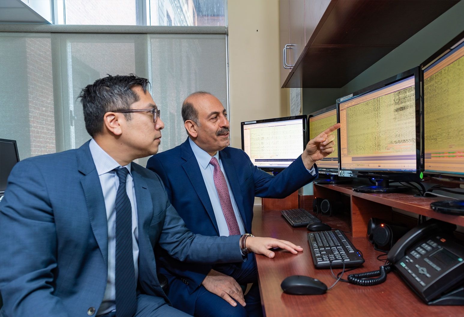 Doctors Najjar and Chong review medical records displayed on computer monitors