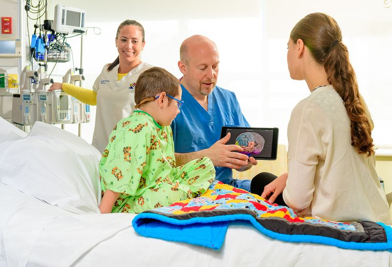 Two medical staff members smile and talk to a 5-year-old male pediatric patient in a bright green hospital gown and his mother, who sits on the hospital bed next to him.