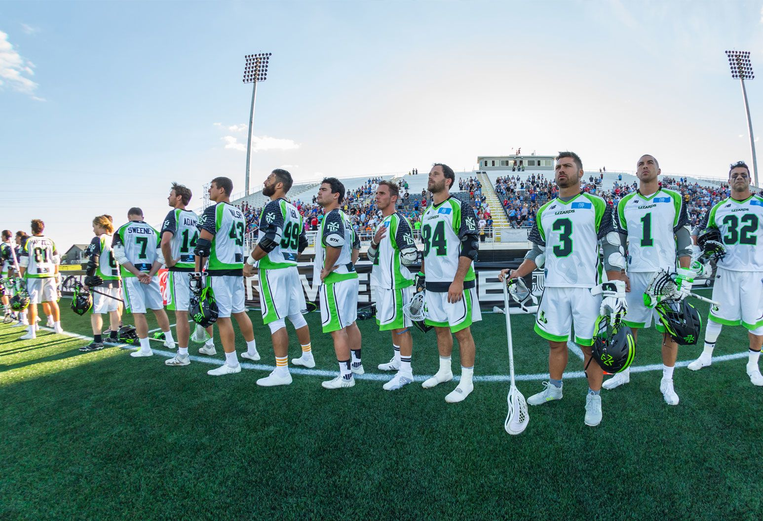 Players on the New York Lizards lacrosse team line up before a game, listening to the National Anthem. Some of them have their hands on their hearts. They wear lime green and white uniforms and hold lacrosse sticks and helmets in their hands. There is a crowd in the bleachers in the background.
