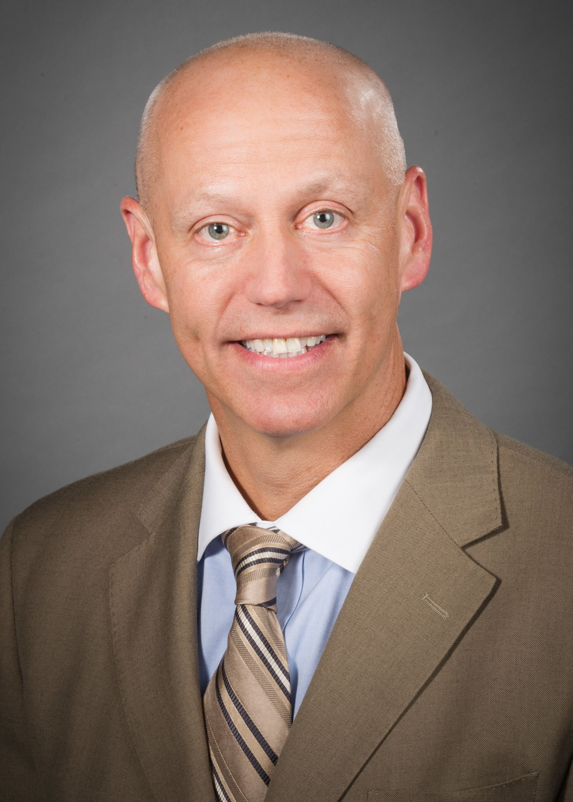 Nick Fitterman, MD, wearing a brown suit, blue shirt and gold tie.