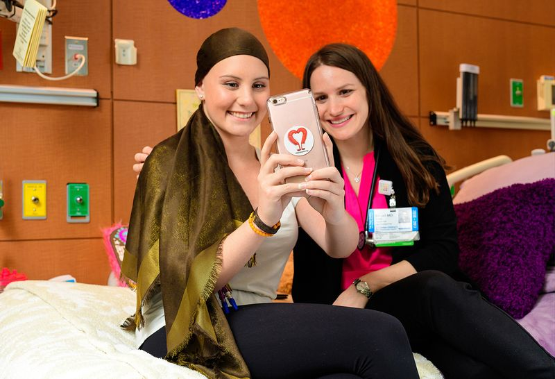 "A smiling teenage pediatric patient wears a long brown head scarf. She sits on a Cohen Children's Medical Center hospital bed next to a smiling young female staff member, and the two take a ""selfie"" together on teen's cell phone."