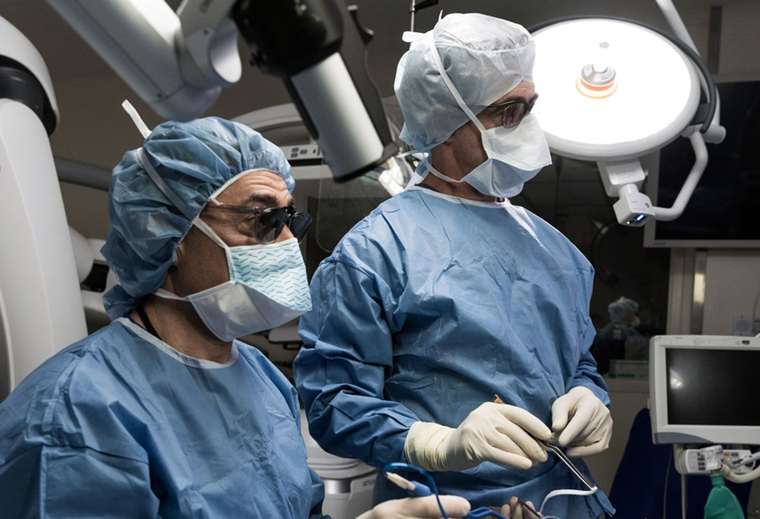 Two surgeons dressed in surgical gowns, masks, and head coverings are looking at a monitor during surgery
