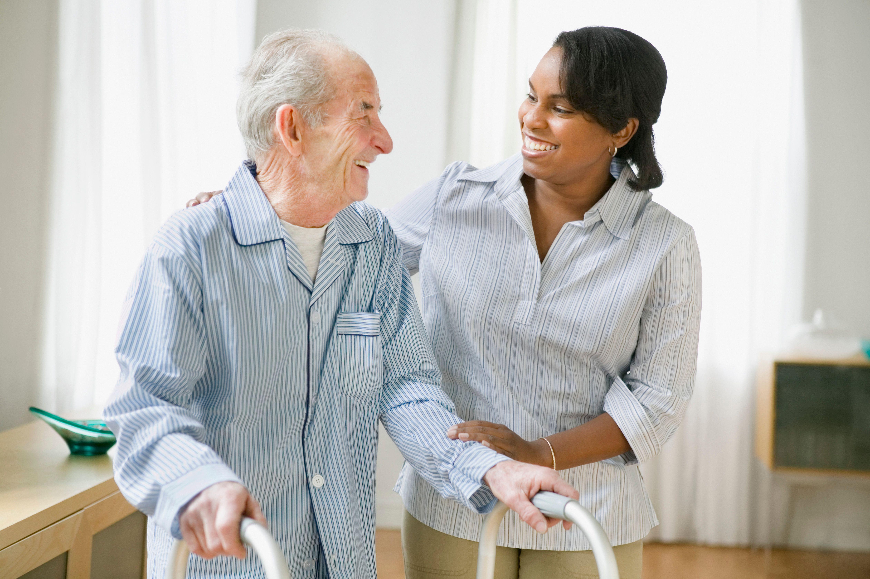 An elderly man walks with a clinician