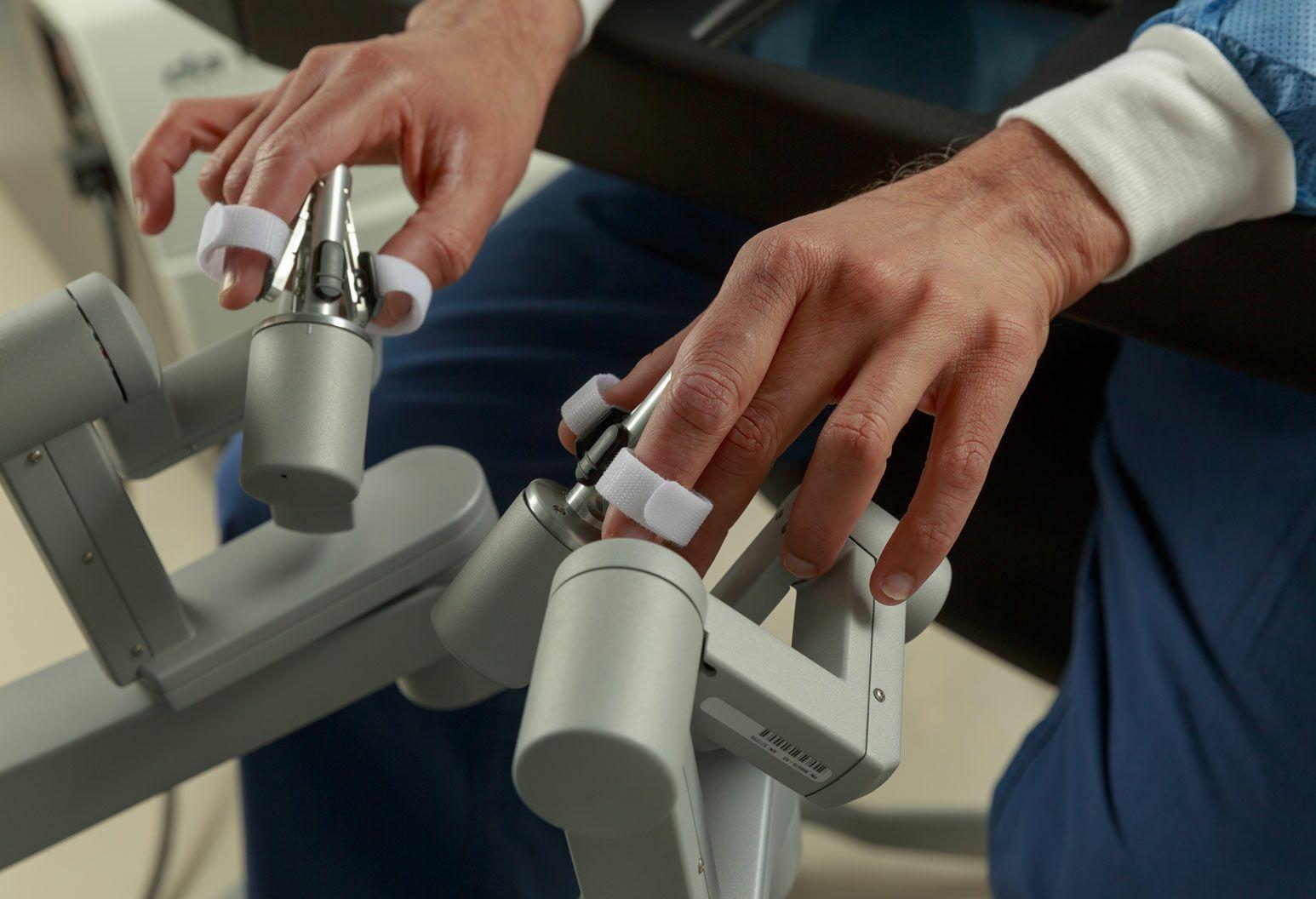 A close up of a doctors hands performing robotic surgery.