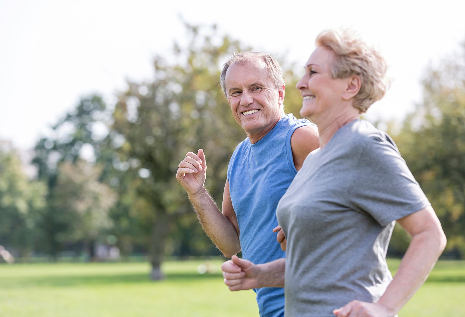 A senior couple jogs together in a park. The man is wearing a blue tank top, looking at the woman. The woman is wearing a gray t-shirt and looks straight ahead. There are trees and greenery in the background.