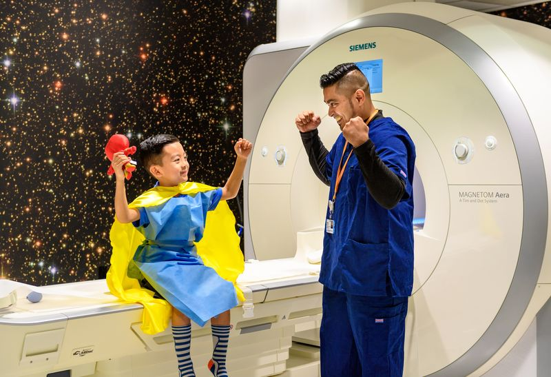 Smiling pediatric patient, about 6 years old, wearing a blue hospital gown, striped socks and yellow super hero cape, while flexing his biceps and holding a red toy in his hand. He is sitting on the MRI machine and the wall behind him features a giant image of twinkling stars. A male staff member dressed in blue scrubs smiles back at him and flexes his own muscles.