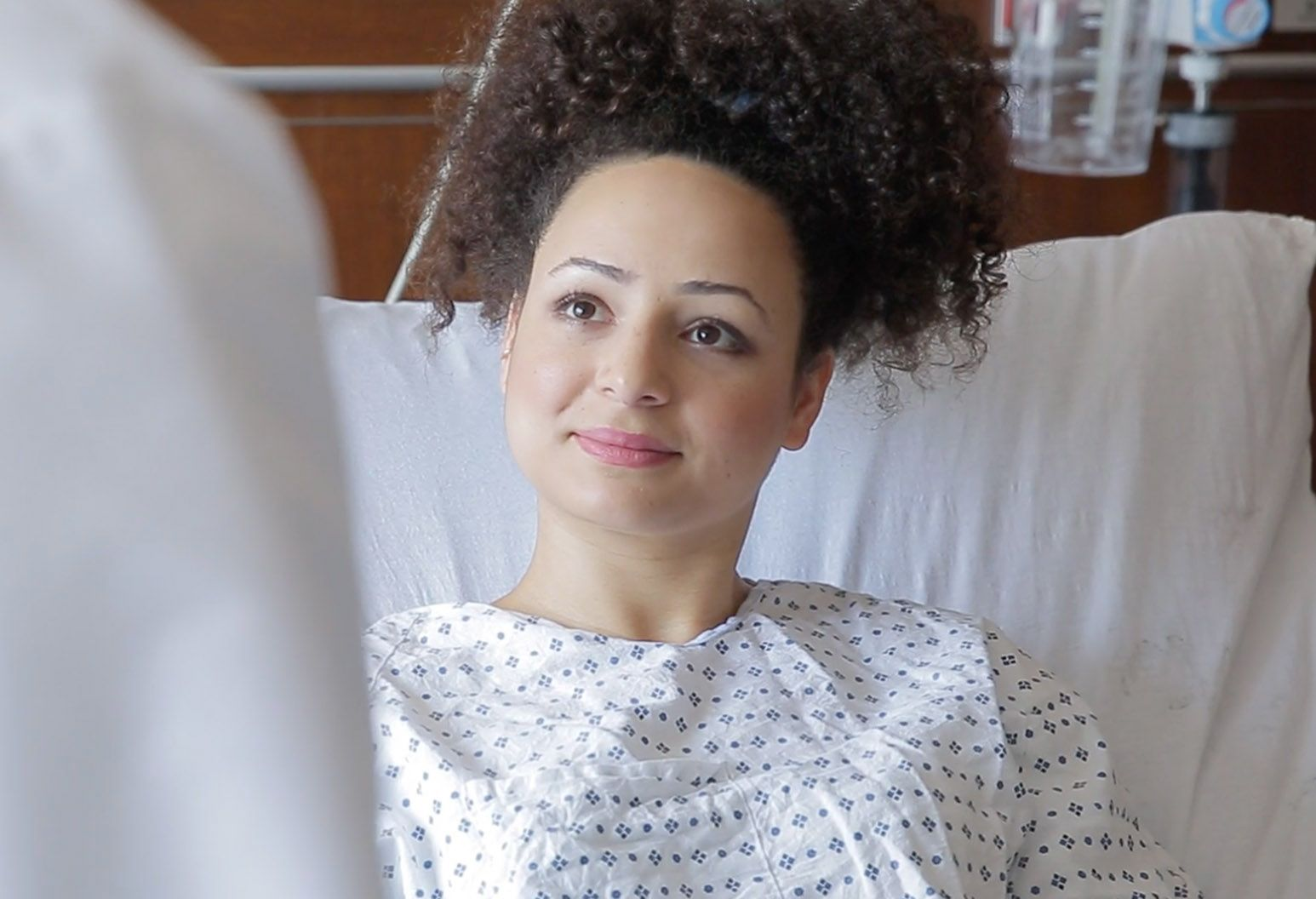 A female patient with dark curly hair wears a medical gown and lies in a bed. She looks up at the doctor (out of frame) for reassurance.