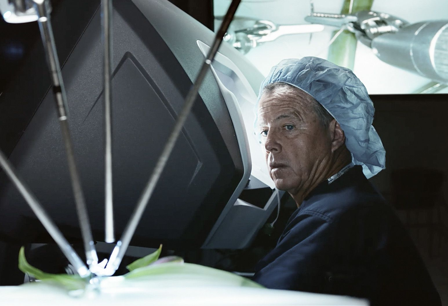 Male surgeon is seen standing next to robotic surgical equipment