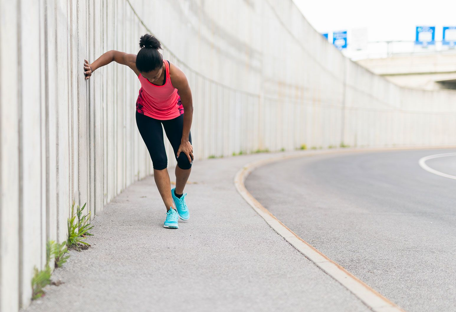 A woman in a jogging outfit leans against a wall outside and she rubs her knee. She is wearing a jogging outfit - pink top, black tights, and aqua blue sneakers.