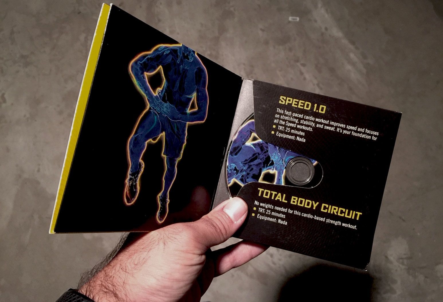 A hand holds a workout dvd in a black case. The case has a graphic of a body in motion in a body thermal view. The other side of the case displays details of the workout.