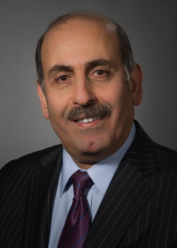 Souhel Najjar, MD, wearing a striped suit, blue shirt and red and blue tie