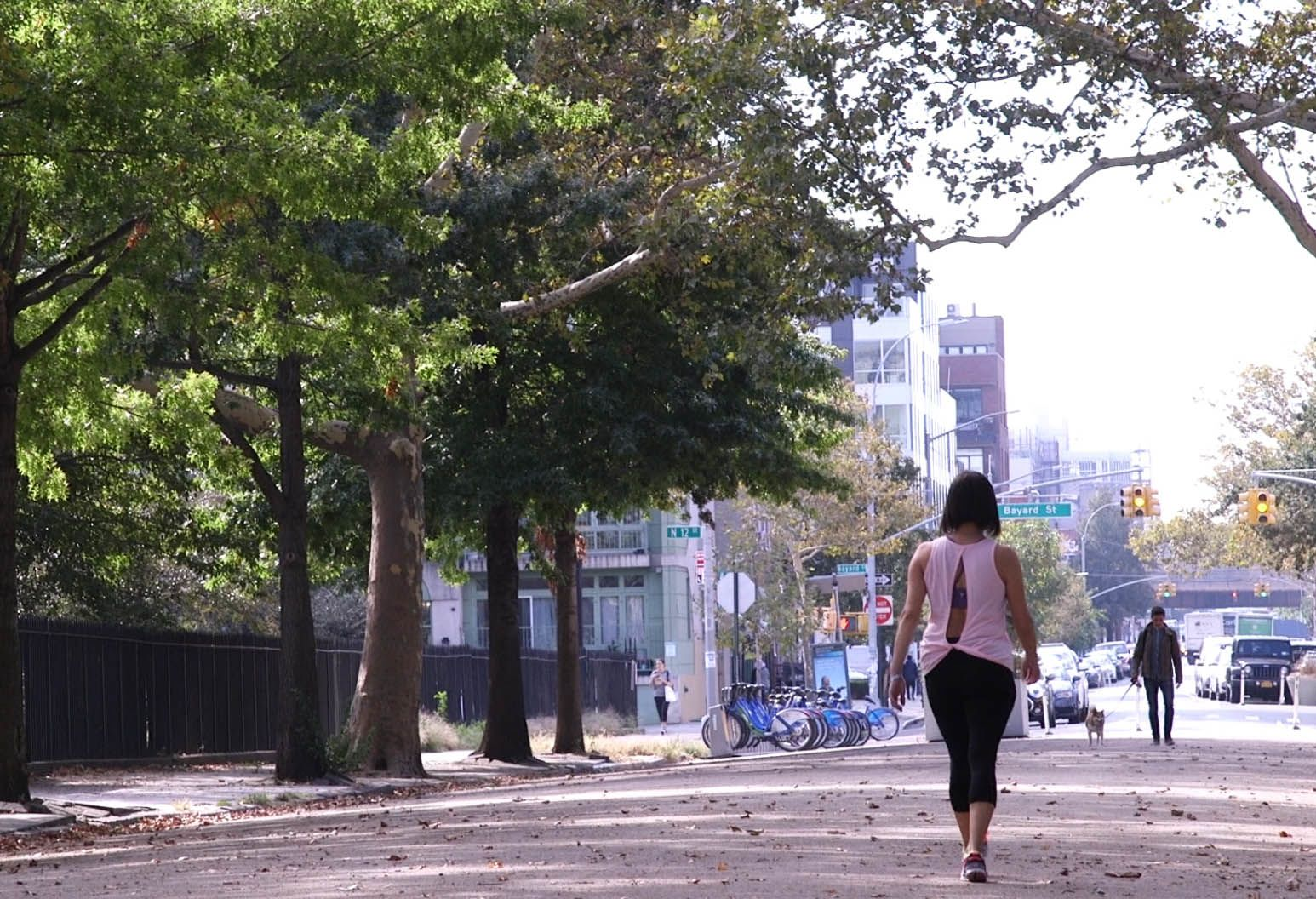 A woman in a pink blouse and black jeggings walks down a city street along a park.
