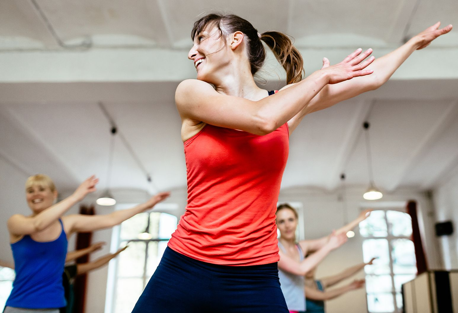 A woman in a read tank top energetically dancing in her dance studio with her class