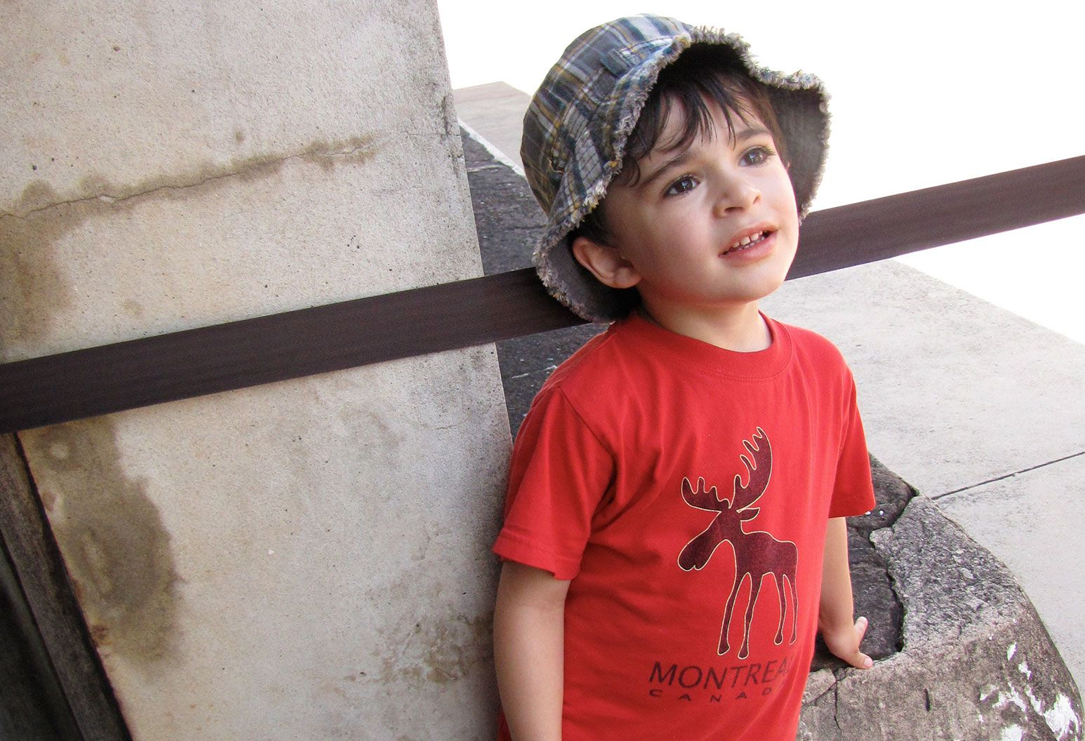 A toddler in a red shirt with a moose print looks off from the camera. He leans on a rock with his as he rests his back on a column behind him.