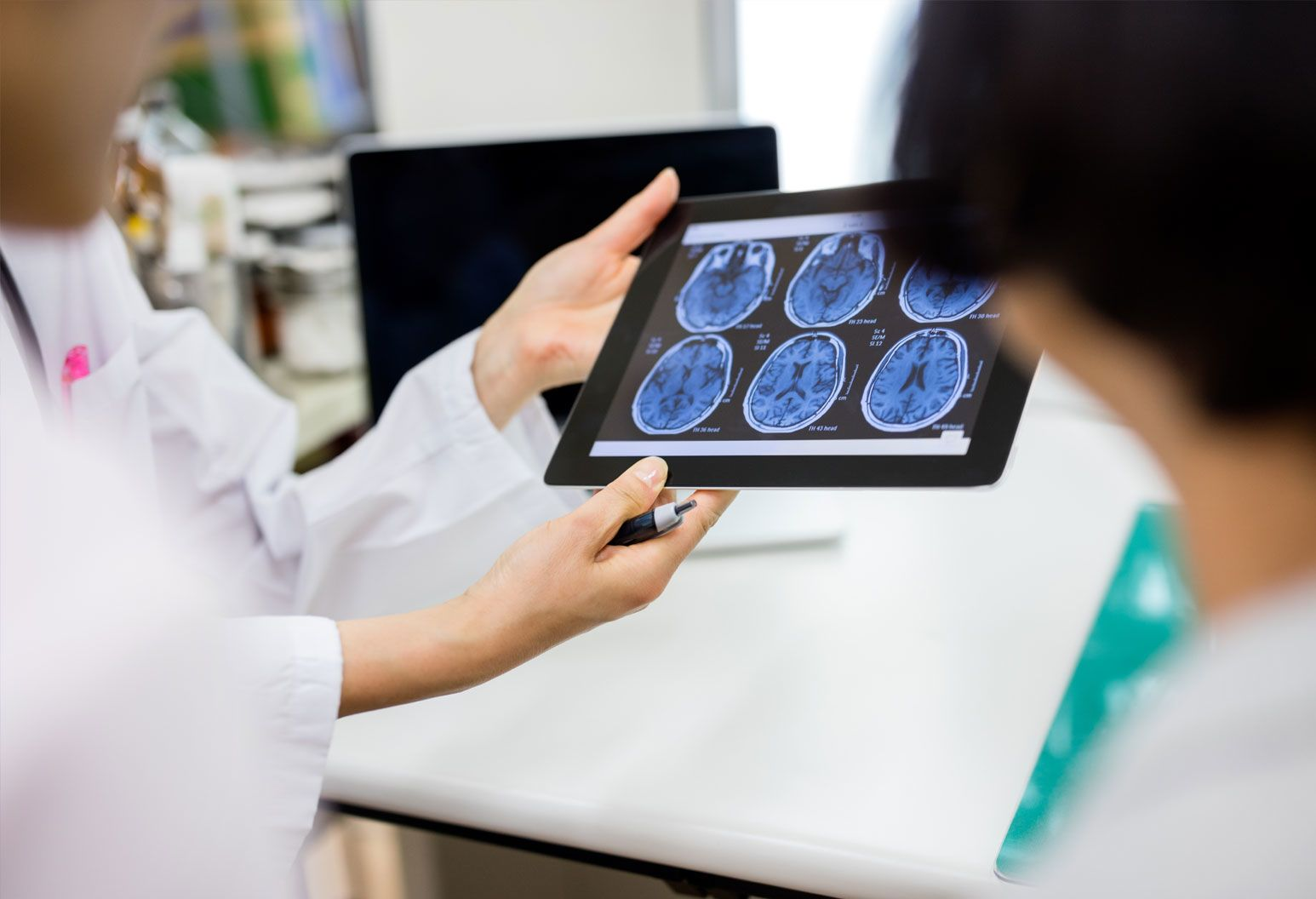 close up of hands holding a tablet with brain scans on it