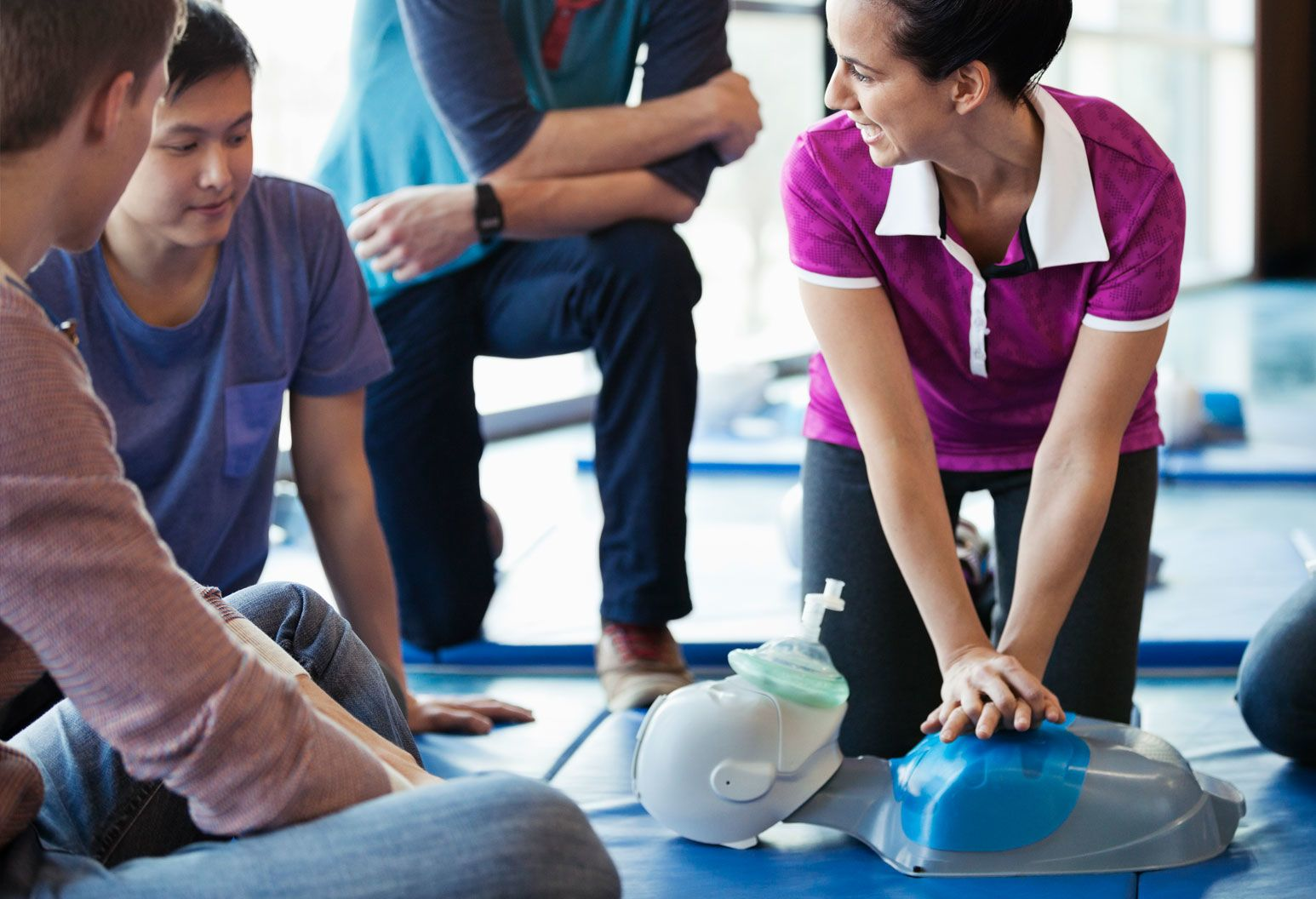 A CPR training, a female student is practicing on a dummy while looking at her classmate for encouragement.