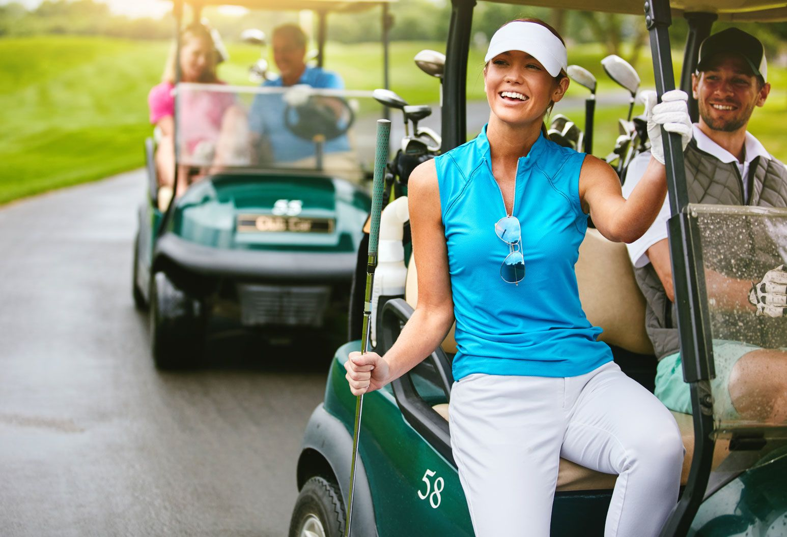 A young couple sits in a golf cart on a golf course. The focus is on the woman, who is wearing a blue top and white visor. She holds a golf club in her hand and is exiting the gold cart.