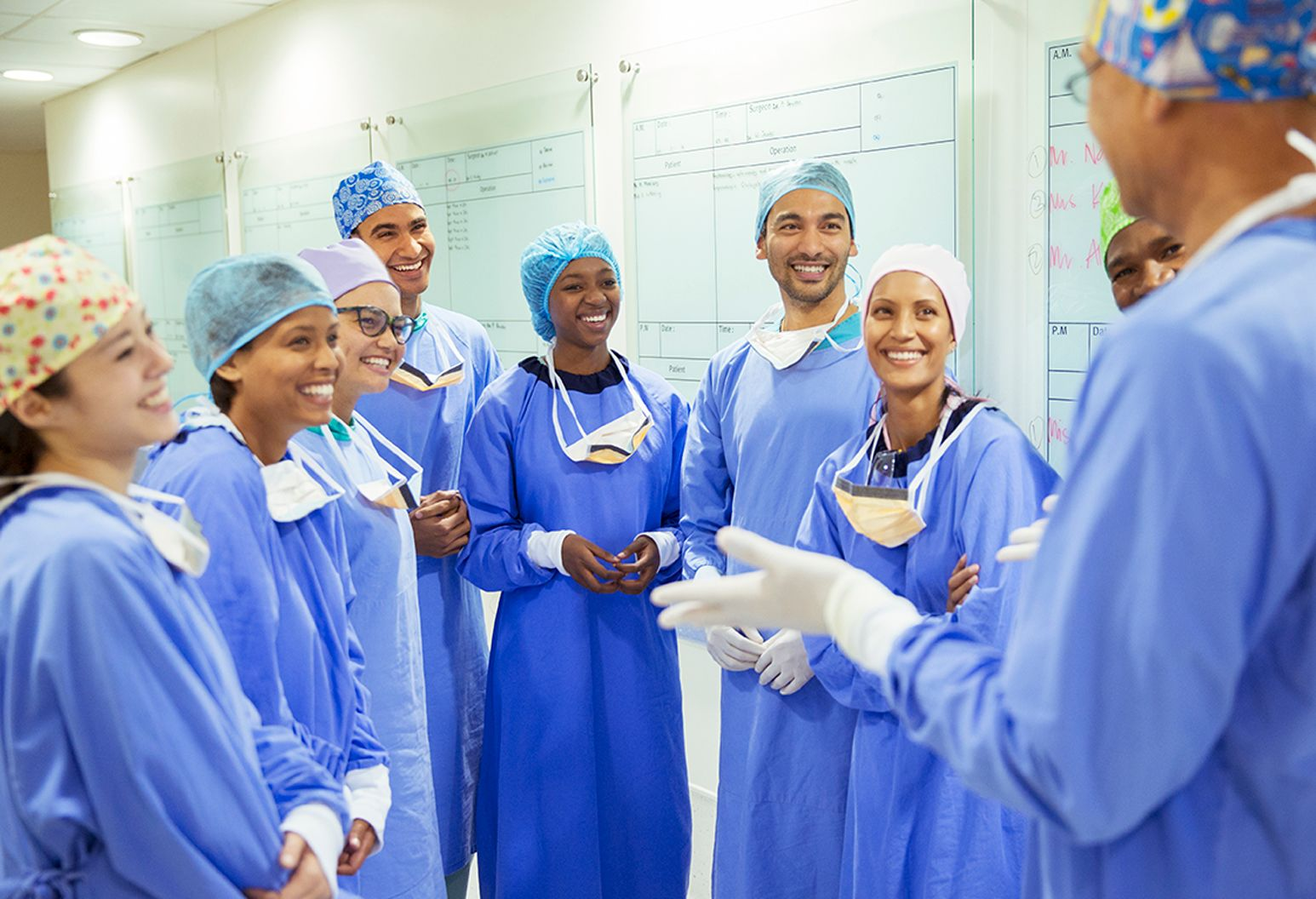 Happy surgery residents in blue scrubs listening to their group leader