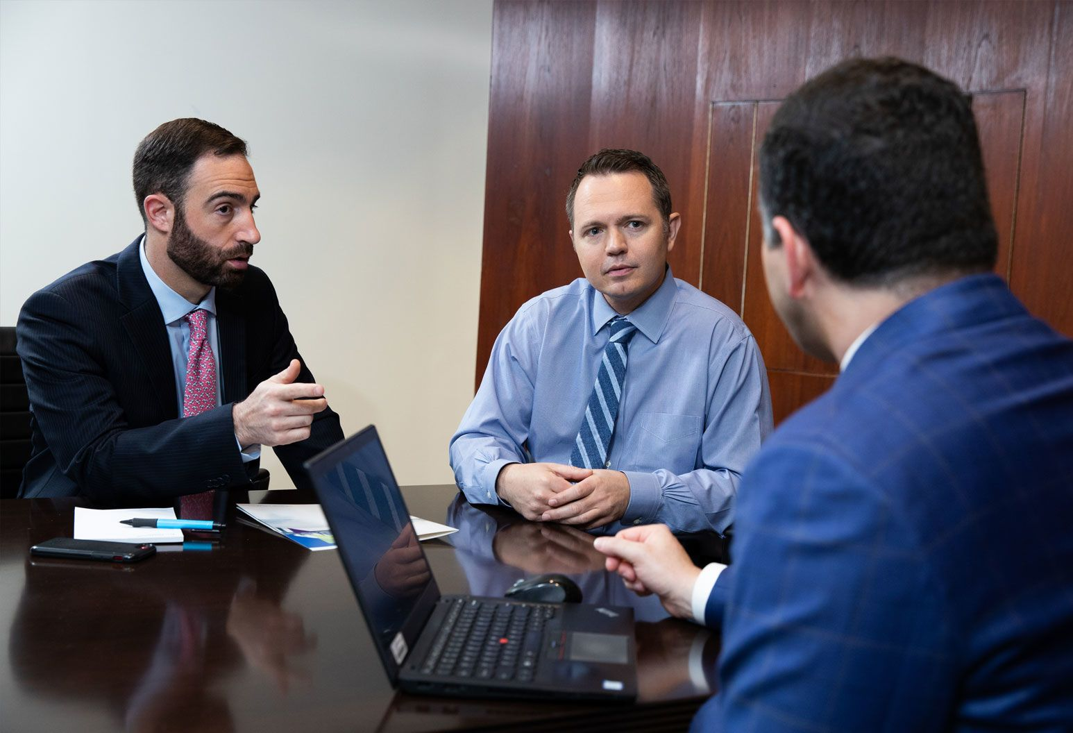 Three male doctors wearing suits sit in a conference room discussing a case. There is a laptop on the table.