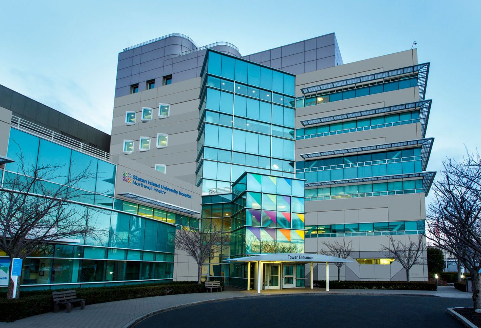 Exterior picture of Staten Island University Hospital, photographed in the early evening with a dark sky and reflection of the trees in the windows