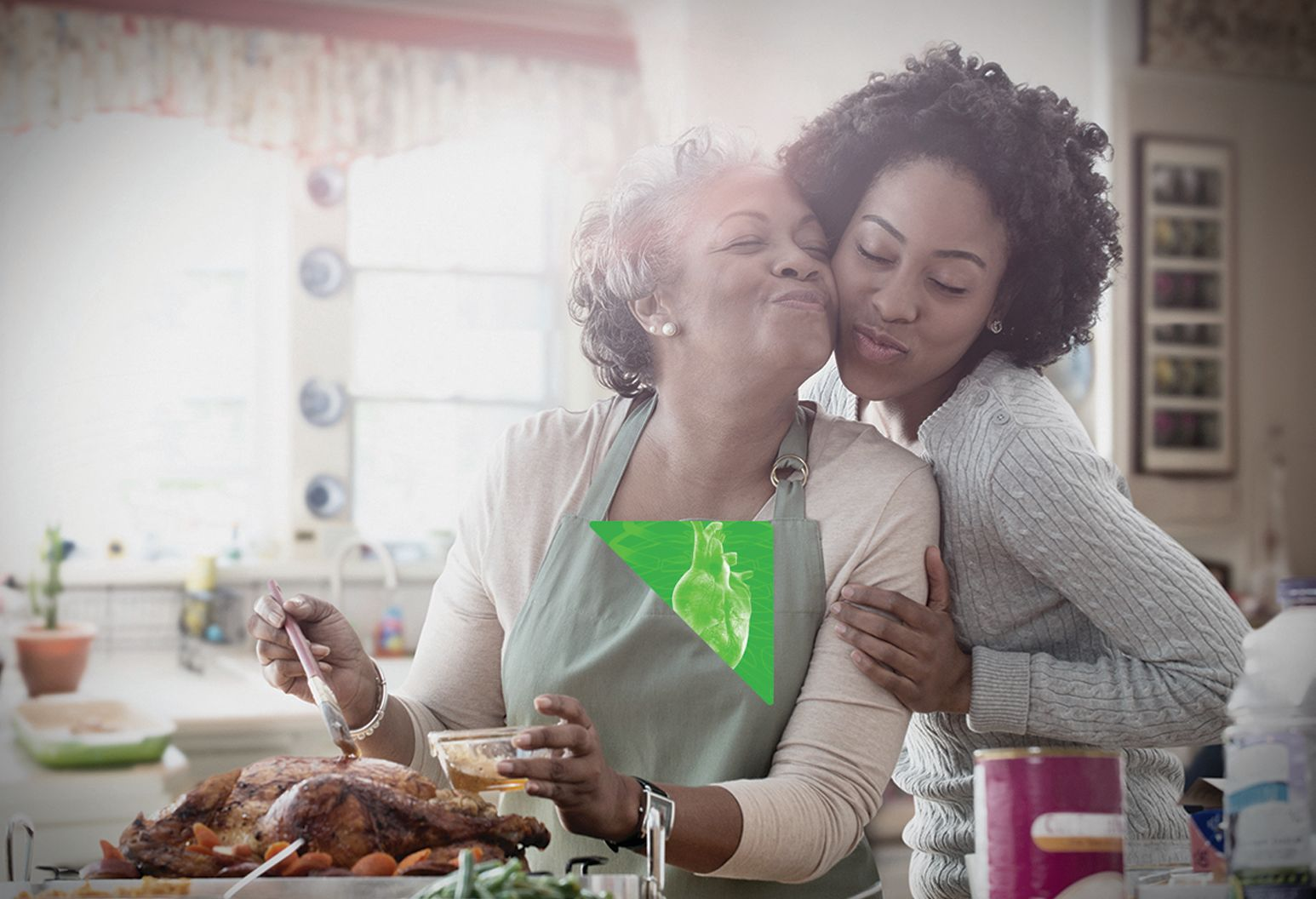 An elderly mother and middle aged daughter embrace in a kitchen while the mother cooks a turkey. There is a green constellation with the graphic of a heart organ over the mother's heart.