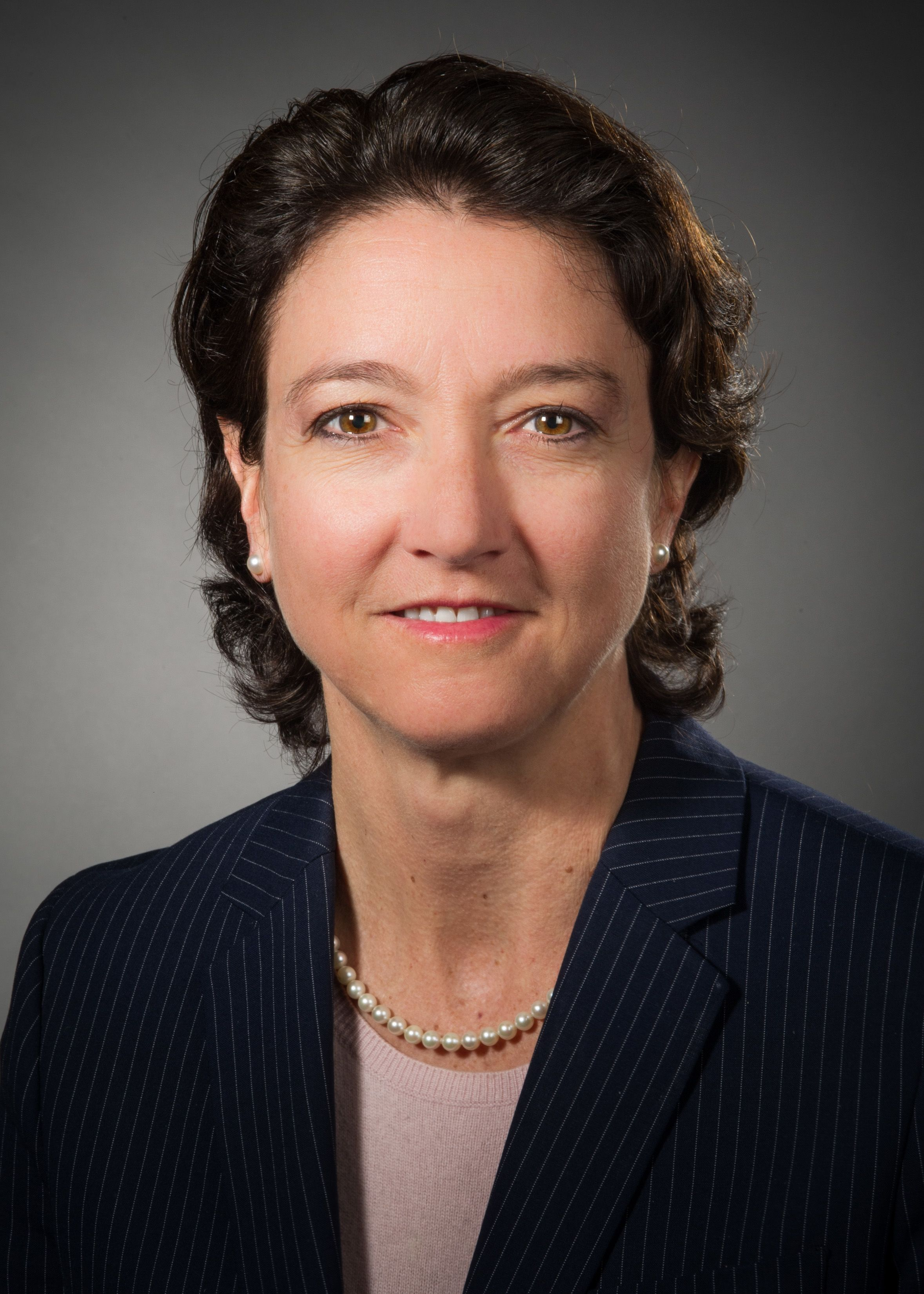 Maria Torroella Carney, MD, wearing a striped suit and purple shirt