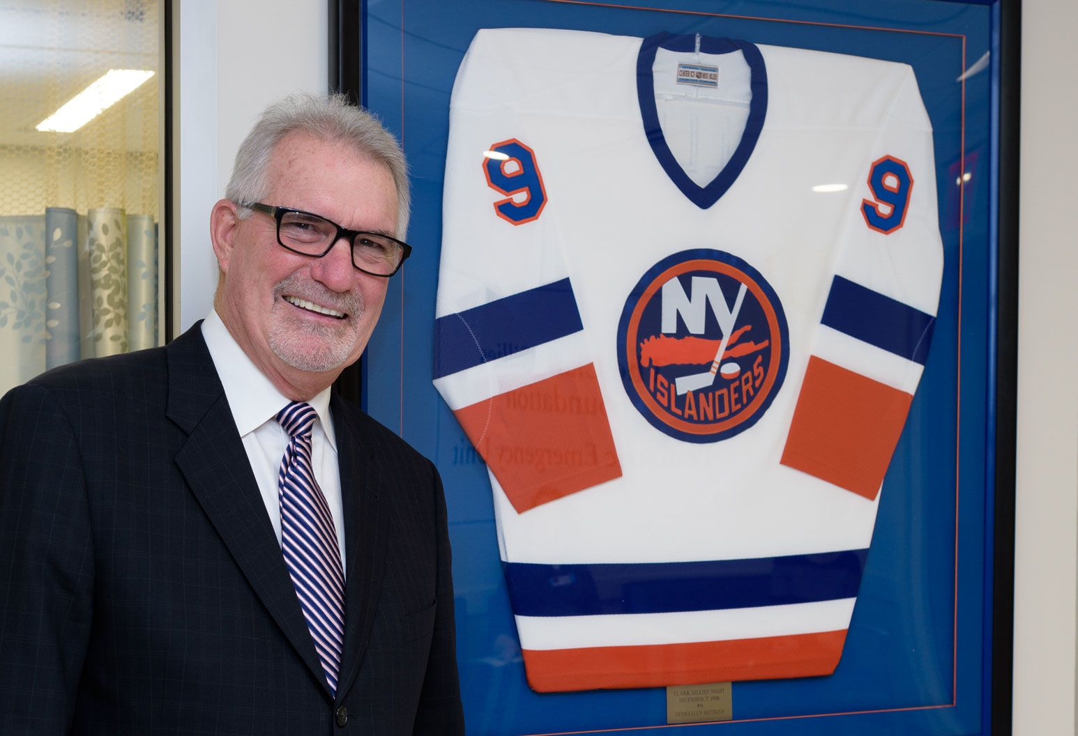 A man in a black suit and glasses smiles in front of a framed New York Islanders jersey.