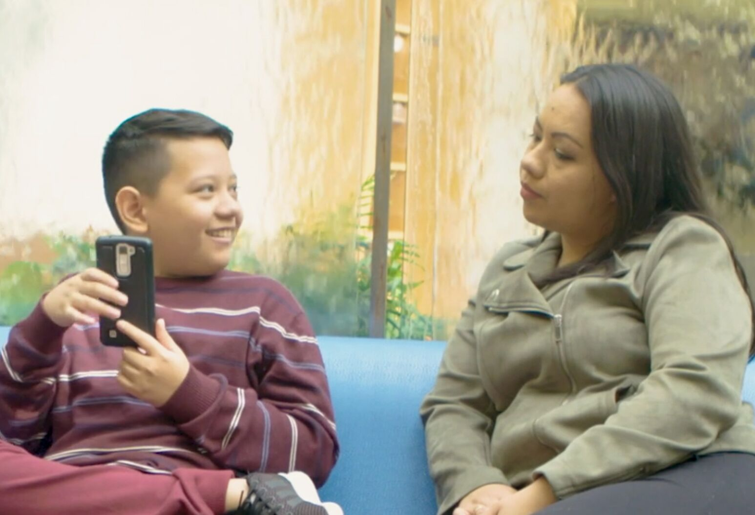 A boy and his mother sit on a couch at Cohen Children's Medical Center and look at each other. The boy is holding a cell phone in his hand.