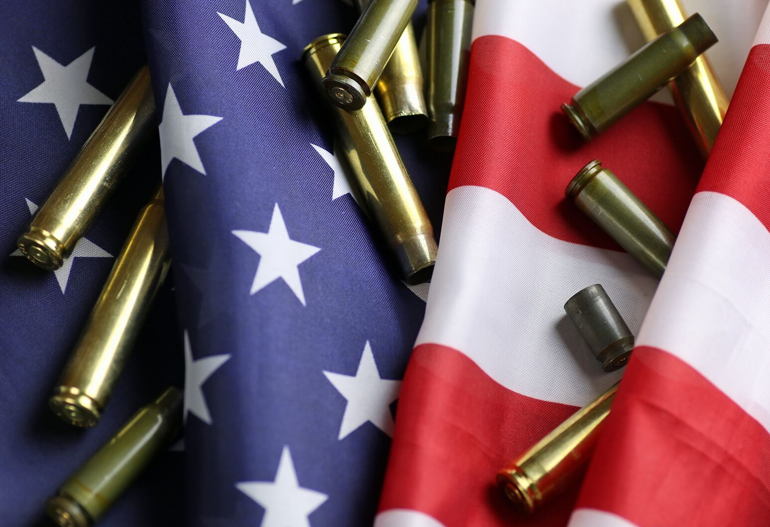 High-caliber bullets are spread out across an American flag. Michael Dowling questions where health care CEOs stand in the fight against gun violence